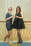Two young woman in masks with glasses of wine Royalty Free Stock Image