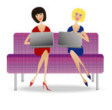Two young woman  with notebook sit on sofa Stock Image