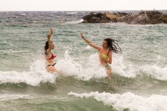 Two young woman playing in the spray of the waves Royalty Free Stock Images