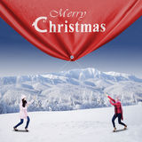 Two Young Woman Pulls A Christmas Banner Royalty Free Stock Image