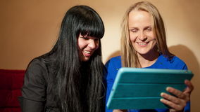 Two young woman reading a tablet-pc. Dolly shot of two attractive young woman blonde and brunette reading a tablet-pc smiling as they look at information or stock footage