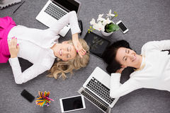 Two young woman relaxing in the office, view from above Royalty Free Stock Photo