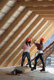 Two young woman repairing the roof of the house Stock Images