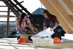 Two young woman repairing the roof of the house Royalty Free Stock Image