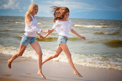 Two young woman running and having fun on the beach Royalty Free Stock Photos