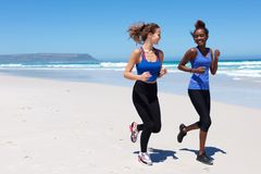 Two young woman running on the sea shore Stock Photos