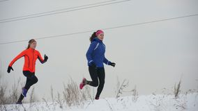 Two young woman running technically in winter outdoor. Sport and leisure concept stock video