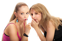 Two young woman sharing secret. Isolated Royalty Free Stock Image