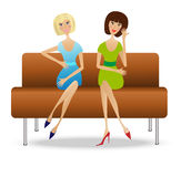 Two young woman  sit on sofa Stock Image
