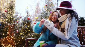 Decorate city street. Two young woman siting on bench at decorated street, girls drinking coffe and looking at colorful christmas toy in hands stock footage