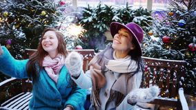 Decorate city street. Two young woman siting on bench at decorated street,portrait girls with sparklers in hands have fun, happy smile stock video footage