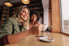 Two young woman sitting at cafe and having coffee royalty free stock image