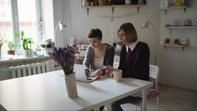 Two young woman sitting at table and using notebook for order online. Two woman shopping online by laptop computer in home. Online shopping concept stock footage