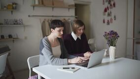 Two young woman sitting at table and using notebook. Woman working on laptop. Two young woman sitting at table and using notebook. Two woman shopping online by stock video