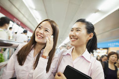 Two young woman smiling and talking on the phone Stock Photography
