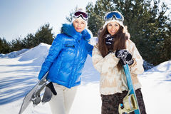 Two young woman with snowboards. Two beautiful smiling girls with snowboards standing outside, sunny winter day Royalty Free Stock Photo