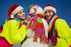 Two young woman with a snowman Royalty Free Stock Photos