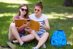 Two young woman study togheter in park, wears casual clothes and sunglasses, read abstracts while prerarig for seminar in royalty free stock photos
