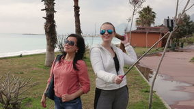 Two Young woman taking self portrait on the seafront using smartphone mobile cell phone camera. stock video