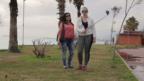 Two Young woman taking self portrait on the seafront using smartphone mobile cell phone camera. stock video footage