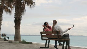 Two Young woman taking self portrait sitting on the seafront using smartphone mobile cell phone camera. Closeup. HD stock video footage