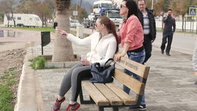 Two Young woman taking self portrait sitting on the seafront using smartphone mobile cell phone camera. Two Young woman taking selfie  sitting on the seafront stock footage