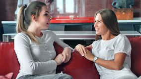 Two young woman talking and chating on red sofa at home.  stock video footage