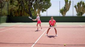 Two young woman tennis doubles players. Two attractive young woman tennis doubles players standing ready to receive the ball on an outdoor all weather court stock video