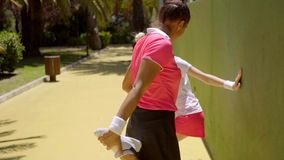 Two young woman tennis players warming up. Two attractive sexy young woman tennis players warming up doing stretching exercises against a wall as they wait to stock footage