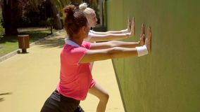 Two young woman tennis players warming up. Two attractive sexy young woman tennis players warming up doing stretching exercises against a wall as they wait to stock video