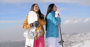 Two young woman with their snowboards. Two attractive happy young woman with their snowboards standing posing and smiling at the edge of a run on a mountain ski stock footage