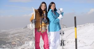 Two young woman with their snowboards. Two attractive happy young woman with their snowboards standing posing and smiling at the edge of a run on a mountain ski stock video footage