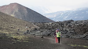 Two young woman tourists walk down the volcano after climbing to top. TOLBACHIK VOLCANO, KAMCHATKA, RUSSIA - JUNE 24, 2016: Hiking on Kamchatka Peninsula - two stock video footage