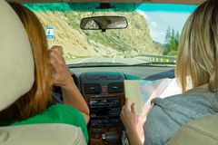 Two young woman travelling by car one in the passenger seat look royalty free stock photography