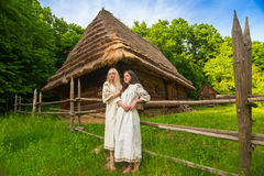 Two young woman in ukrainian national costumes. Two young women in ukrainian national costumes near old wooden house (wide angle lense Stock Photos