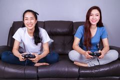 Two young woman using joystick controller playing video game on Stock Images