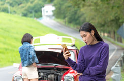 Two young woman using mobile phone while looking at broken down car. On street royalty free stock photo