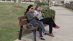 Two young woman using a smart phone, outdoors on sitting on the wooden bench in park. stock footage