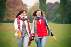 Two young woman walking in autumn park. Two pretty girls having fun in the park Stock Image
