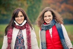 Two young woman walking in autumn park. Two pretty girls having fun in the park Royalty Free Stock Photo