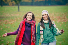 Two young woman walking in autumn park. Two pretty girls having fun in the park Royalty Free Stock Photography