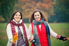 Two young woman walking in autumn park. Two pretty girls walking in the park Royalty Free Stock Image