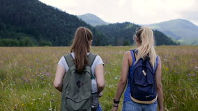 Two young woman walking on mountains stock footage