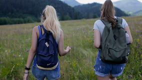 Two young woman walking on mountains stock video