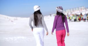 Two young woman walking in a winter ski resort stock footage