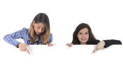 Two Young woman with white board for advertisement. Two young woman, one Brazilian and one caucasian holding and pointing to white board for advertisement Royalty Free Stock Images