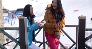 Two young woman on a winter ski vacation stock video