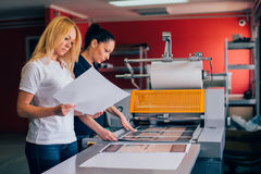 Two young woman working in printing factory. Two young women working in printing factory. Printing Press Royalty Free Stock Images