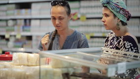 Two young womans choosing spices in grocery section at supermarket. Two young womans have a discussion when choosing spices in grocery section at supermarket stock video