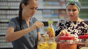 Two young womans choosing spices in grocery section at supermarket. Two young womans have a discussion when choosing spices in grocery section at supermarket stock video footage